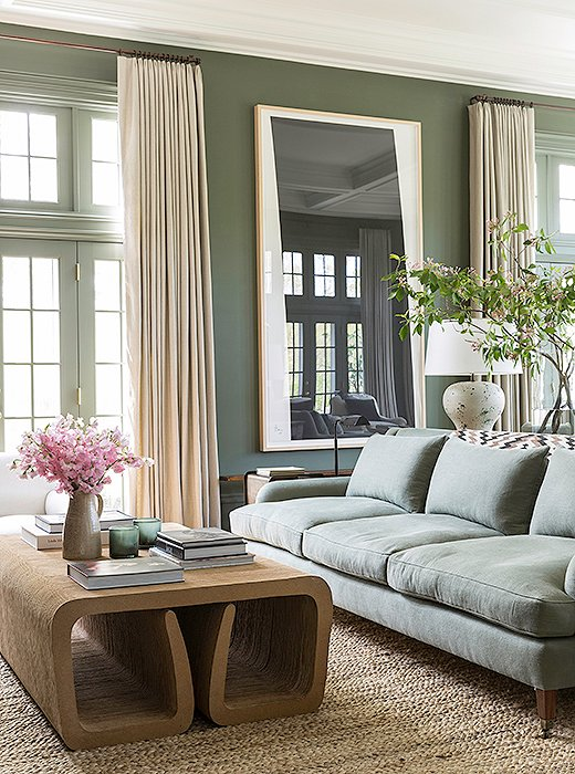 The muted green sofa, and even the darker green walls, are neutrals in keeping with the rest of the room. Photo by Lesley Unruh.