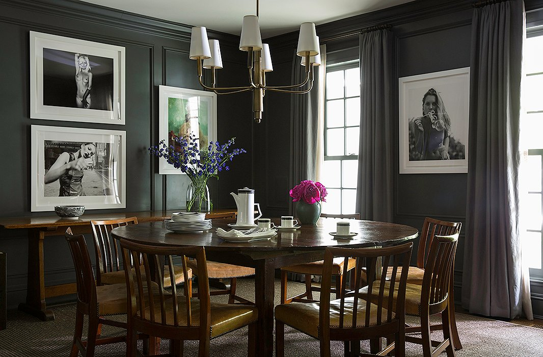 The minimal and moody gray dining room is accented with edgy photographs of Kate Moss.