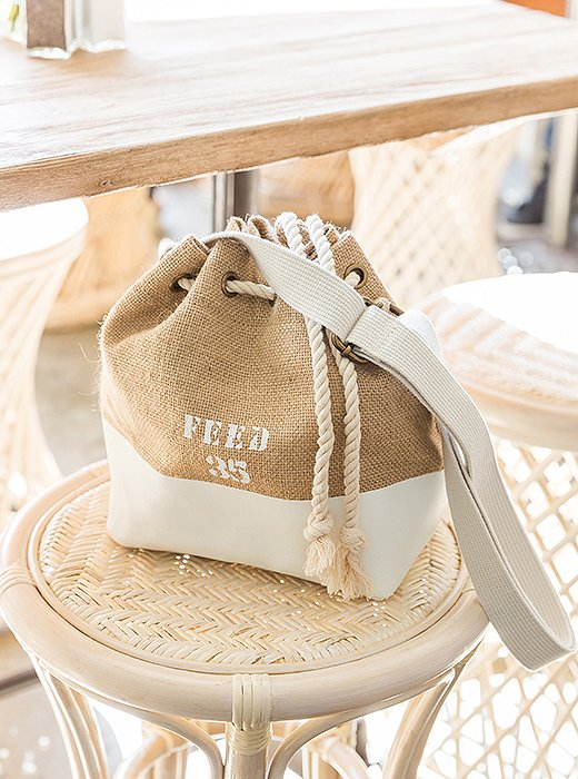 Part of FEED's newHide Tide summer collection, this mini bucket bag features broken-in straw and color-blocked canvas. Every bag purchase provides 35 meals for children around the world.