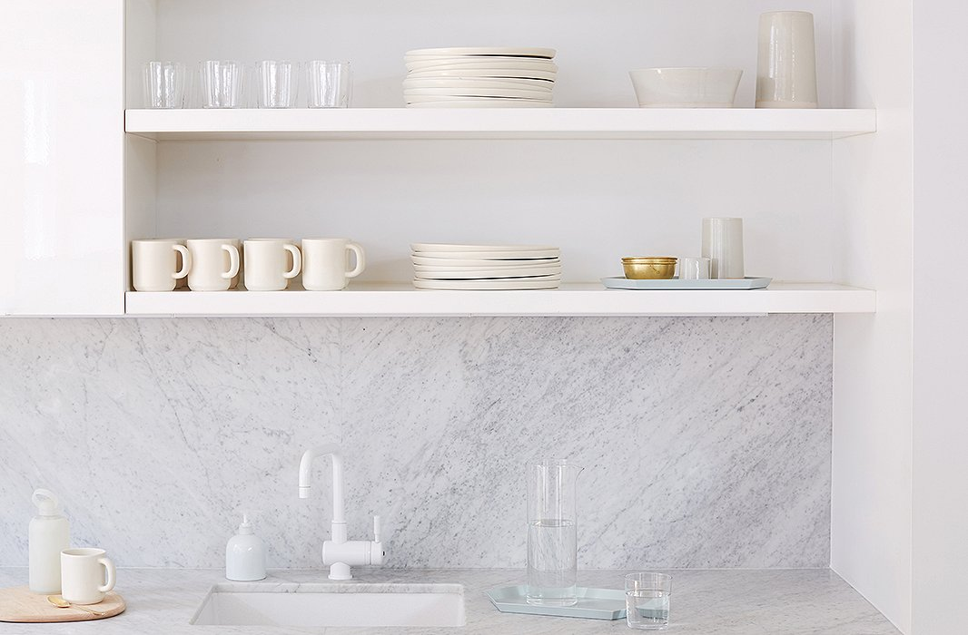 The kitchen is as crisp as can be with marble countertops and white dinnerware.