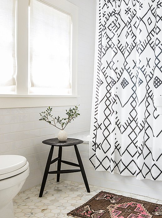 A small Persian rug and a petite black stool add a little contrast to the ultrawhite bathroom.