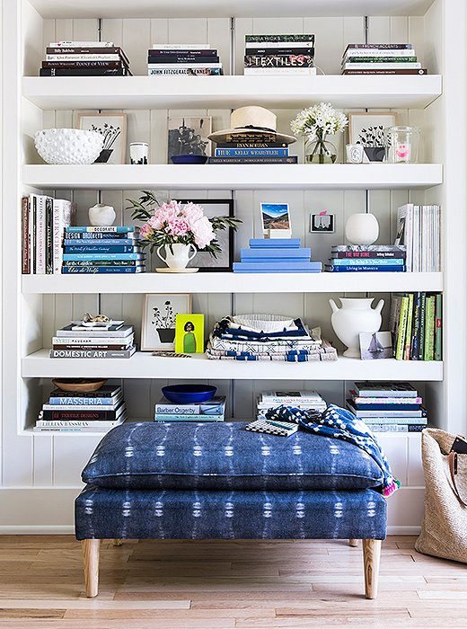 An indigo-printed ottoman lends a lovely touch of color to this space—one that plays perfectly off the palette of blue and white on the bookshelf. Photo by Lesley Unruh.