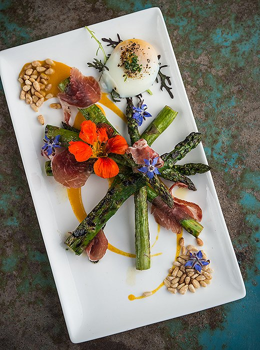 Farm-to-table fare at The Lark includes grilled West Coast asparagus made with preserved Meyer lemon, soft poached egg, spicy coppa, pine nuts, and marigold blossoms. Photo by Rob Stark Photography.