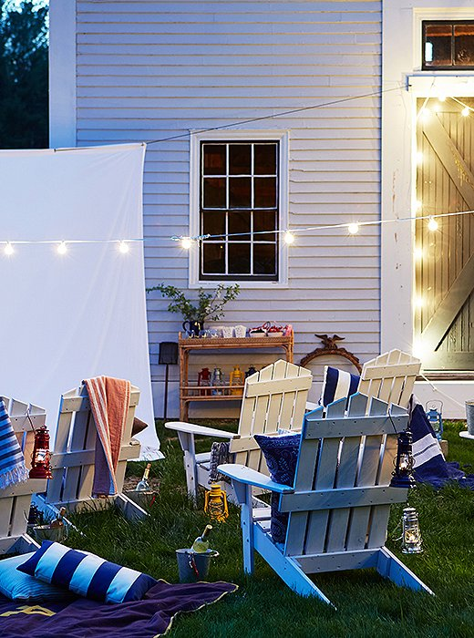 String lights bring an air of magic to any space. Replicate the rest of this cozy look with Adirondack chairs, outdoor pillows, and blankets.