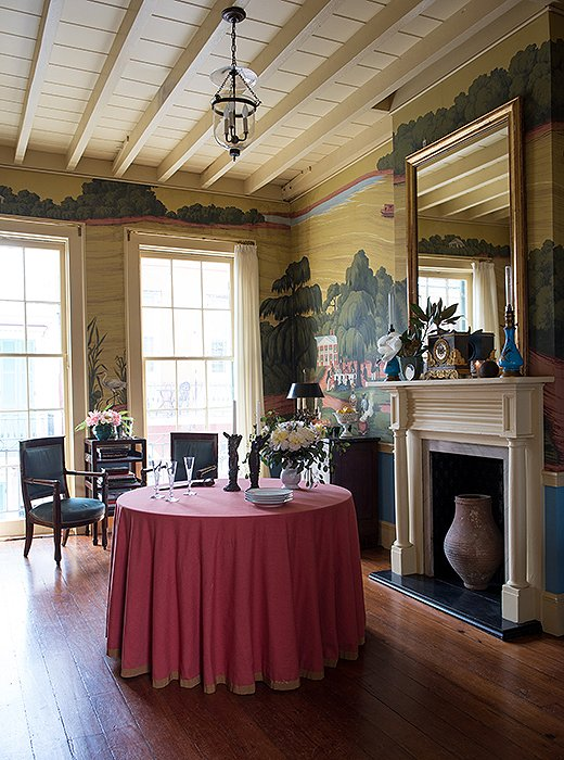"Thomas set up the parlor room to function like a salon, with the furniture positioned around the edges, as was the custom in homes in the past. ""It's a multipurpose room,"" he says, noting that the table can easily be moved. ""We'll have drinks before dinner here and do projects on the round table—everything from making Mardi Gras costumes to little art projects."" See similar skirted round tables here."