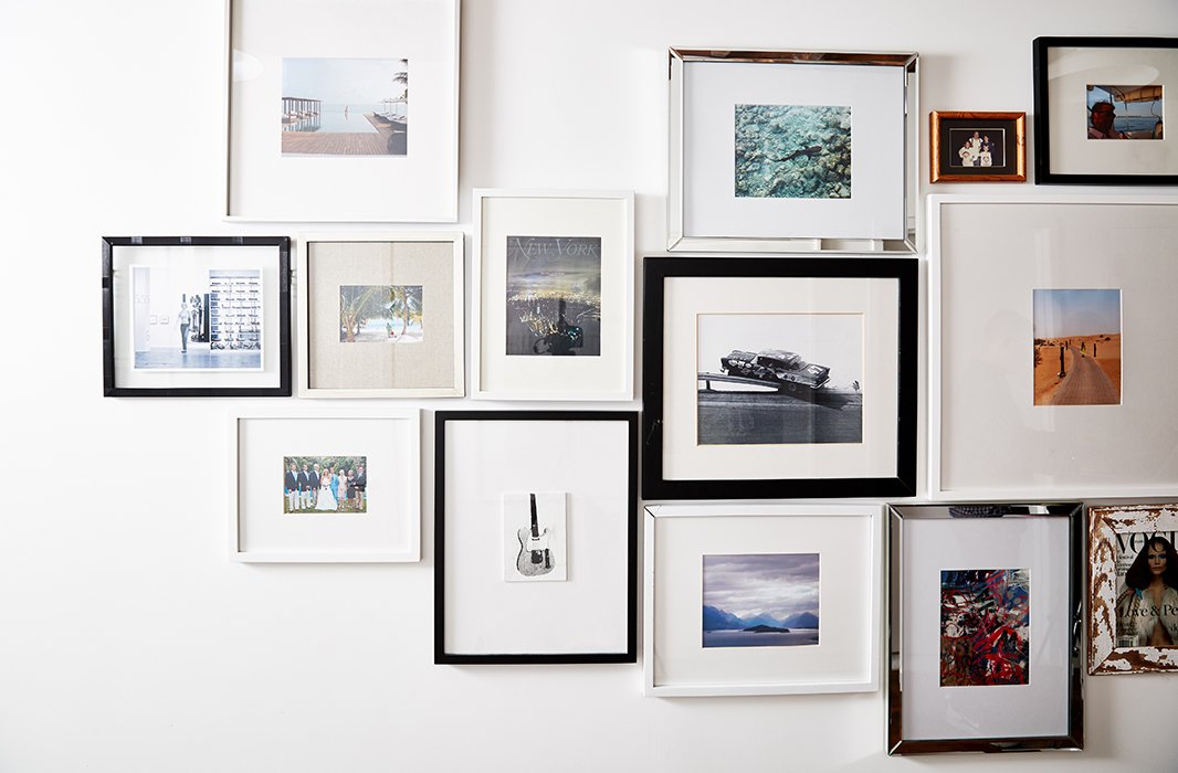 The gallery wall in the couple's master bedroom showcases photographs from their travels as well as special personal moments.