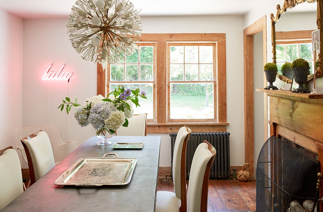 In the dining room, Jennifer blends a mix of styles, from a midcentury glass Sputnik chandelier to an industrial dining table to a trendy neon light fixture emblazoned with her daughter's nickname.