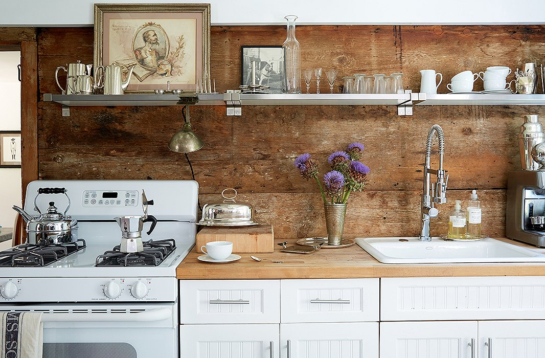 Along with butcher-block counters and stripped wood-plank walls, this kitchen has another element common to farmhouse-style kitchens: open shelving. Though these shelves are industrial steel, they don't detract from the overall effect. Photo by Tony Vu