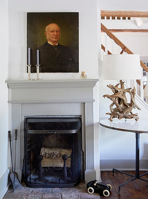 An antique oil painting hangs above the living room's very petite fireplace.