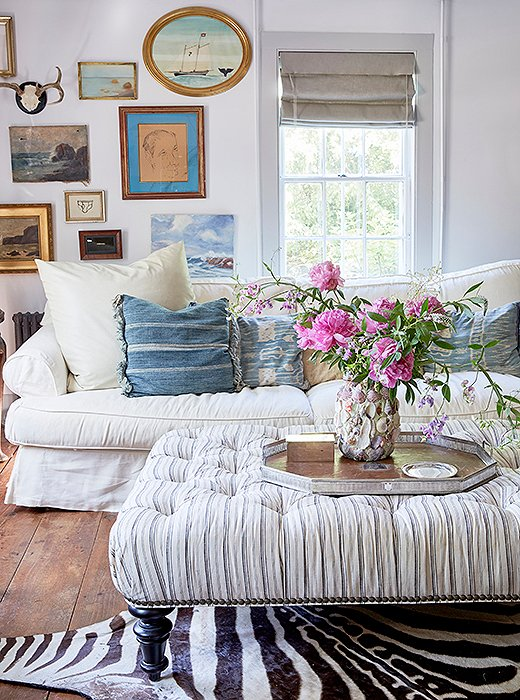 Behind her sofa, Jennifer has created a gallery wall of small framed vintage nautical paintings—a subtle nod to the home's proximity to the Long Island Sound.