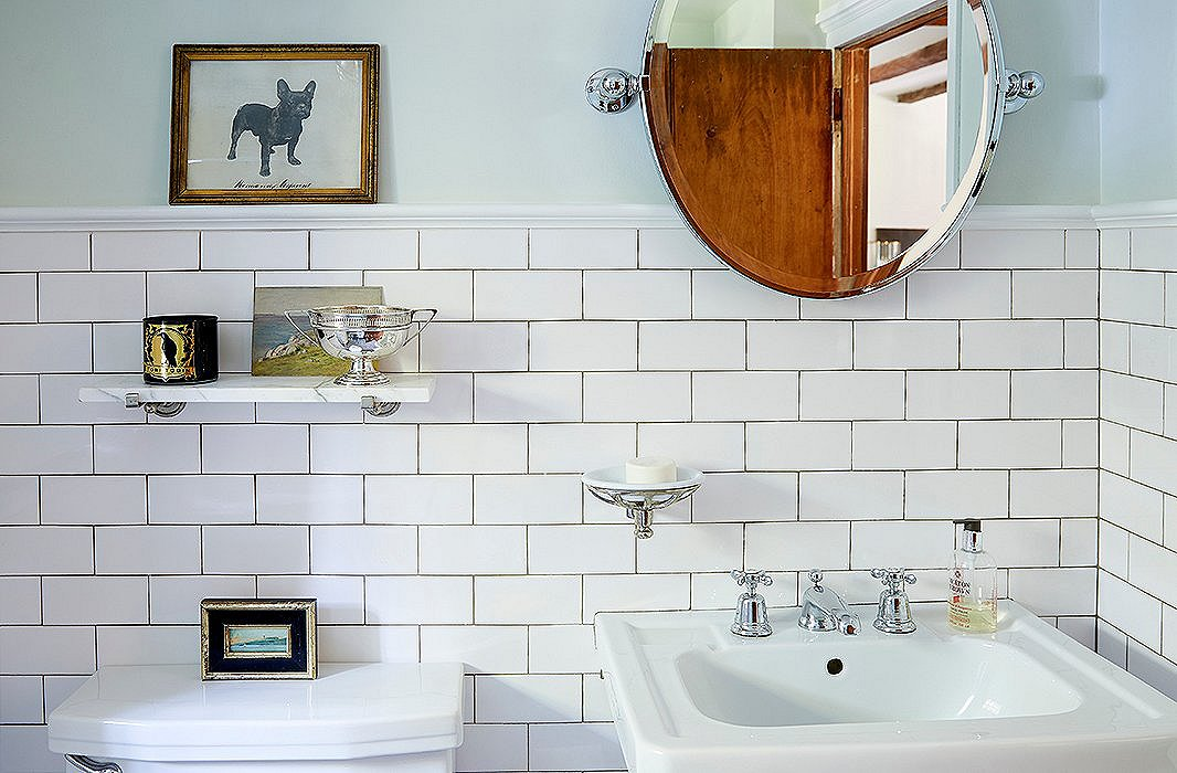 "The bathroom was painted in a baby-blue faux-woodgrain pattern when the couple purchased it. In addition to tiling it, they painted the walls ""a sort of Ladurée green. It's just really soft and gives it a little bit of character,"" Jennifer says."