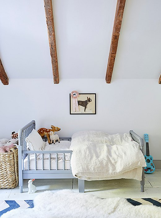 Tallulah sleeps in a pale blue vintage-inspired spindle bed.