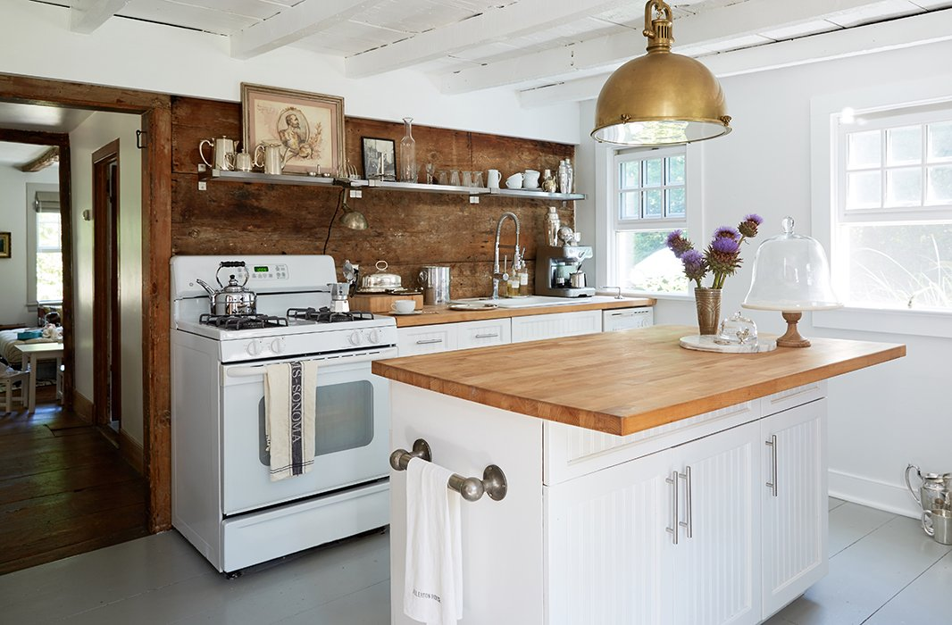 "The Millers' kitchen most recently had faux-granite countertops on maple cabinets. ""We just resurfaced [the countertops] with cheap Ikea butcher block, painted the cabinets, and changed the hardware."""