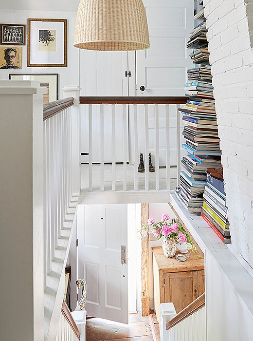 Stacks of books add personality to the stairway landing.