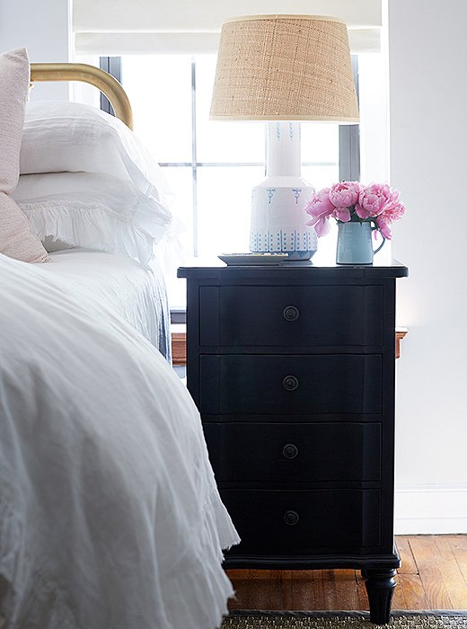 "Cole loves the addition of the nightstands. ""I call these my gift with purchase,"" she says. ""They're tall and have three deep drawers. And with the lamps, they make such a pretty little vignette."" A shallow tray is the perfect perch for earrings or hand cream."
