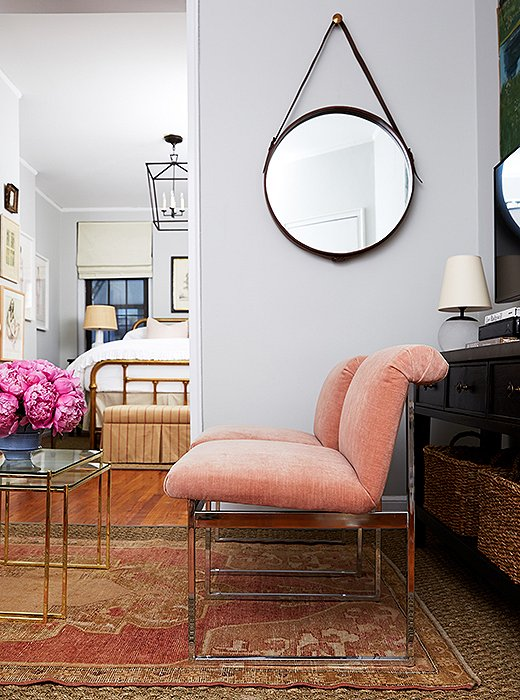 Cole originally wanted light pink walls. Fearing it might read nursery, Alex painted the room with Benjamin Moore Gray Owl and found a pair of Milo Baughman chairs in a blush hue that picks up on the pink tones in the rug.