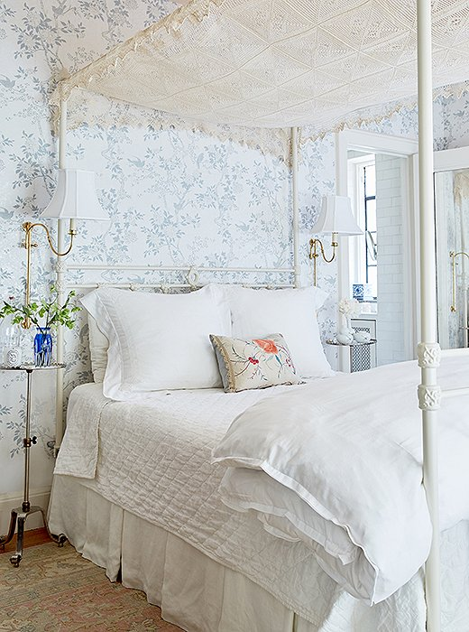 "The designer tells us her favorite finds for the space are the bedside tables in the master bedroom: ""There's really no space for a queen bed and two tables, so they're just drink tables. They're so tiny. They're so cute. They have a scalloped edge and are nickel with little brass threads that lift them up or down so you pick the height."""