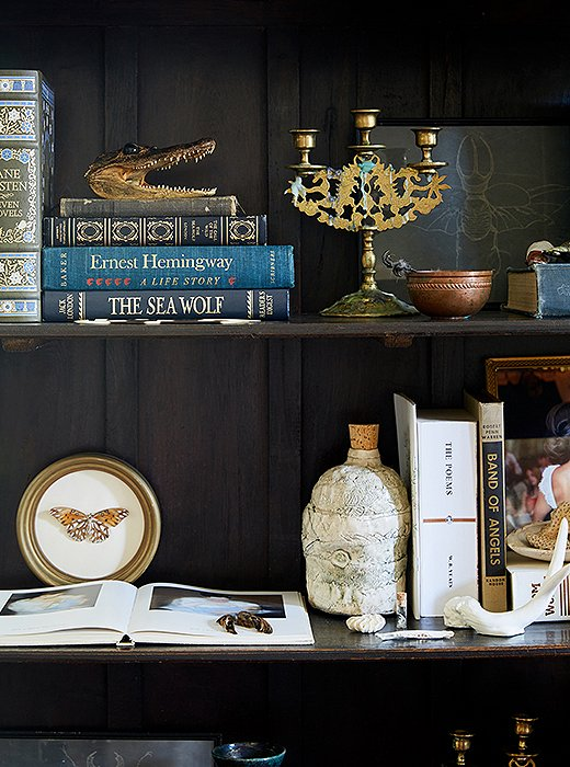 Kate's shelves are beautifully styled with vintage books, small paintings, antique candleholders, and small works of art.