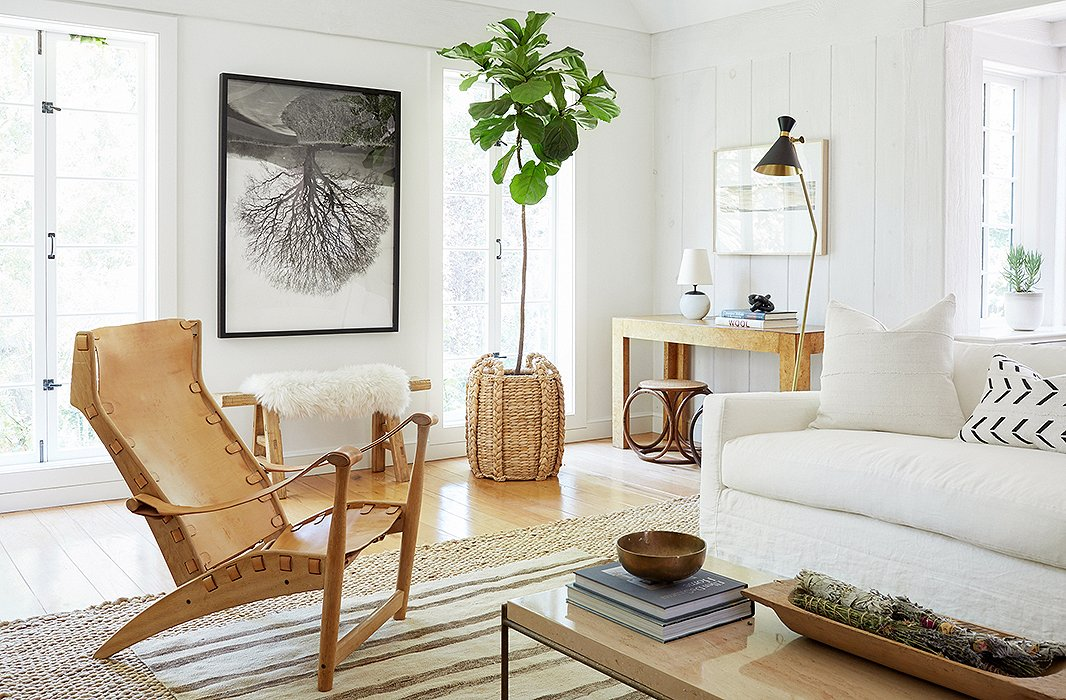 "The house was a blank canvas, but Jenni had set aside a few pieces from her previous home that she thought might end up working in the space. ""Jenni had a great collection of vintage leather chairs that I definitely wanted to incorporate,"" Alex tells us. ""We thought a supersimple slipcovered sofa in white would work well with them, and we also brought in a lot of vintage pieces to pull the look together."""