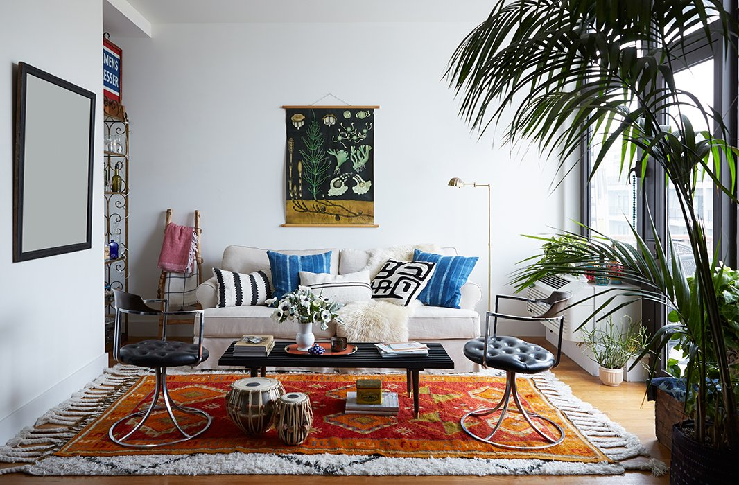 The apartment's living room illustrates the home's colorful, collected aesthetic, with a German teaching scroll, lush layered rugs, mud-cloth pillows, and a pair of midcentury swivel chairs.
