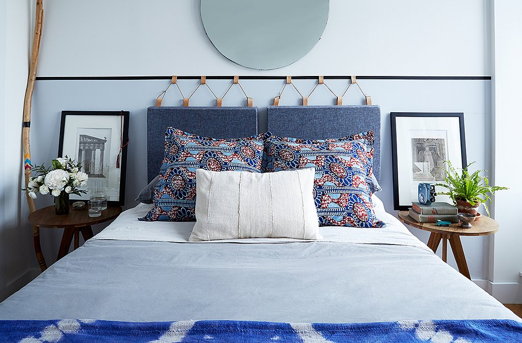 """For the bedroom (aka """"a square white box""""), the couple went minimalist. """"If you are going to keep it minimal, invest in really nice linens,"""" says Rosie.A DIY fabric-and-leather headboard(read the how-to here) is unique and provides all the polish and warmth of a traditional headboard while taking up just three inches of depth."""
