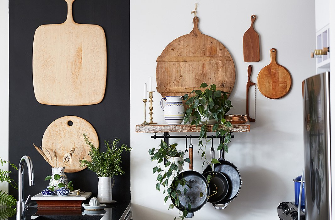 A mod black-and-white kitchen needed some organic ingredients. Enter an array of vintage cutting boards. Rosie approached the project as if it were a gallery wall. A hanging pot rack was practical (they cook a lot) and looks great.