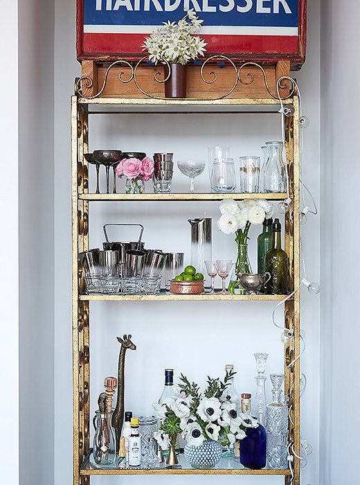Rosie and Ambi, both big entertainers, found a perfect recessed corner in the living room for a salvaged étagère that holds their collection of vintage glassware and barware.