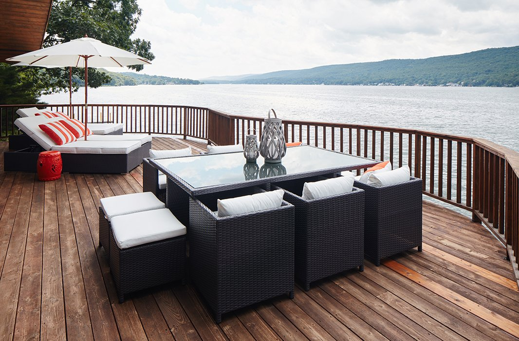 """The family loves to be by the lake, so creating comfortable outdoor spaces was key. Just outside the view room, the lido deck, as the family calls it, was furnished with double chaisesand a dining area that seats 12. """"We did a lot of outdoor wicker,"""" Nicole notes. """"Everything had to be no maintenance and no fuss. If they didn't come to the house for a few months, nothing was going to get ruined."""""""