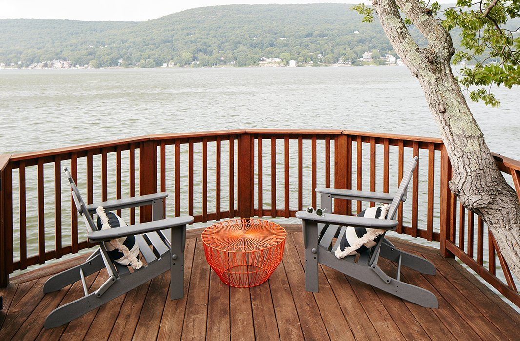 The Adirondack chairs on the middle deck are the perfect spot to take in the lake views. Nicole added outdoor pillows and an orange table for a pop of color.