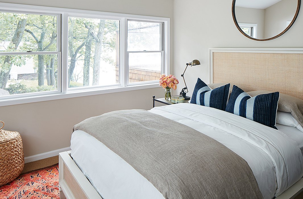 Simple side tables and lighting and neutral linens givethis guestroom an open, tranquil feel.A vintage rug brings in color; a large mirror (similar to this one)draws the eye up.
