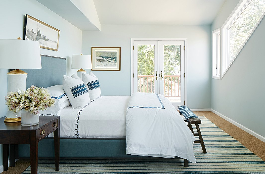 "Nicole chose a pale-blue palette—a nod to the mother's favorite color—for the master bedroom. The narrow space was divided into sleeping and sitting areas. Crisp linens and vintage pillows dress the elegant bed. ""The clients are very sophisticated but also very casual and relaxed,"" says Nicole. ""Every room had to be a mix of that."""