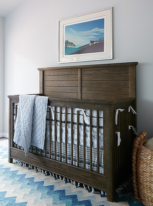 "A gym was transformed into a cheery kids' room with a crib and a sofa with a trundle bed. A bright vintage rug tops the spill-friendly carpet tiles. ""We wanted to make it a light, fresh, fun room but with plenty of space in the middle for them to play,"" Nicole explains."