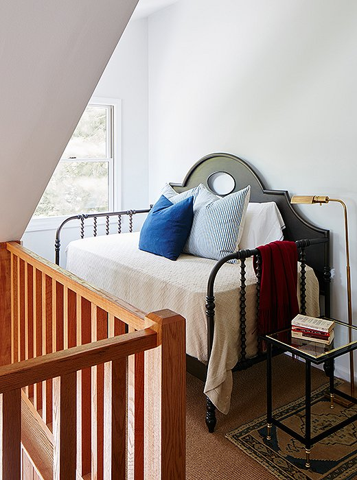 Every square foot of the house was maximized to sleep as many people as possible. Even the landing can host overflow guests: The daybed, side table, and floor lamp create anextra bedroom in an often-underutilized space.