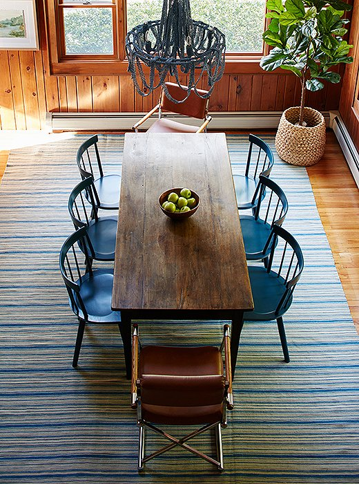 The dining room's long vintage table can fit a crowd.The blue lacquered chairs (durable for little ones!) and vintage leather armchairs elevate the look.