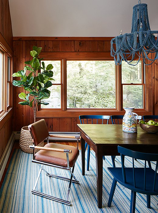 The beaded chandelier and the vintage rug pair perfectly with the blue dining chairs.Thewood paneling was left unpainted to add traditional warmth to the room.