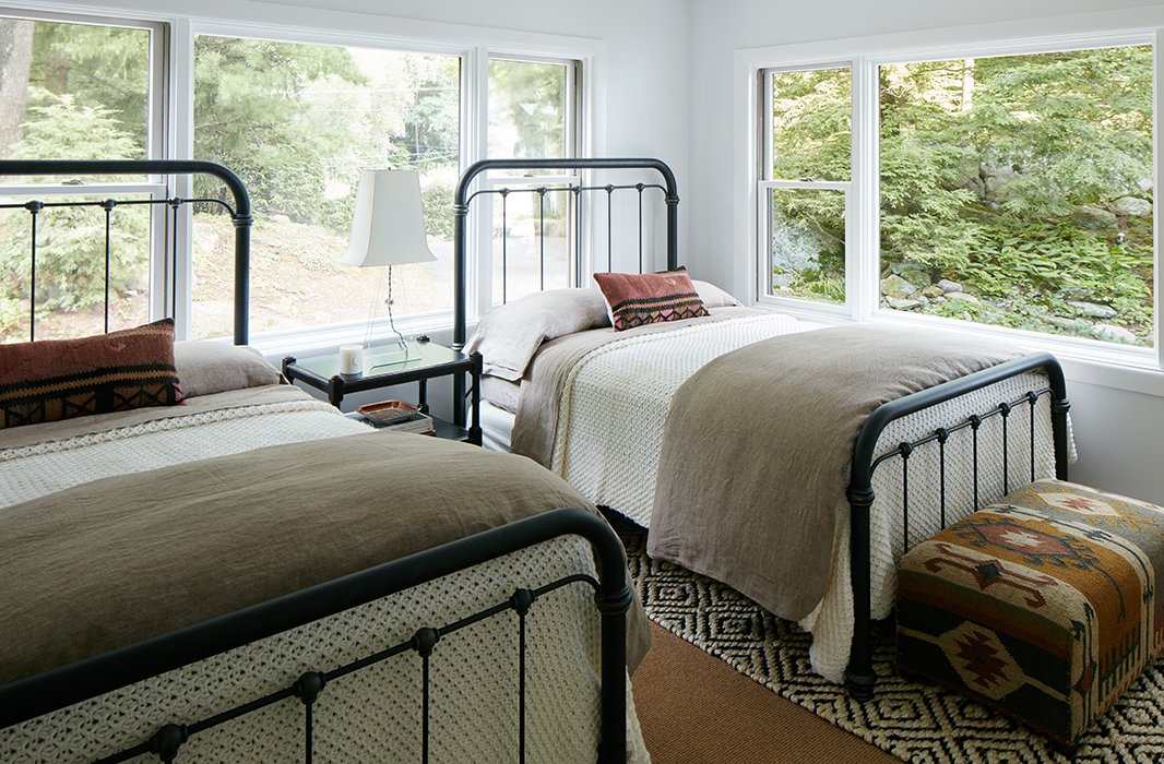 """The twin guest rooms were designed to be durable and low maintenance. """"Anyone could come in there after a day on the lake and not feel like they're ruining anything,"""" Nicole says. Cozy knit blankets and pillows made withvintage textiles warm up the iron beds. The designer used a """"completely foolproof"""" jute rug on the floor."""