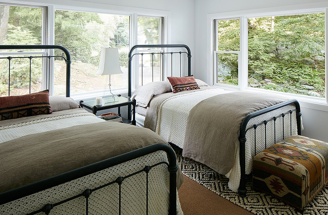 "The twin guest rooms were designed to be durable and low maintenance. Cozy knit blankets and pillows made with vintage textiles warm up the iron beds. The designer used a ""completely foolproof"" jute rug on the floor."