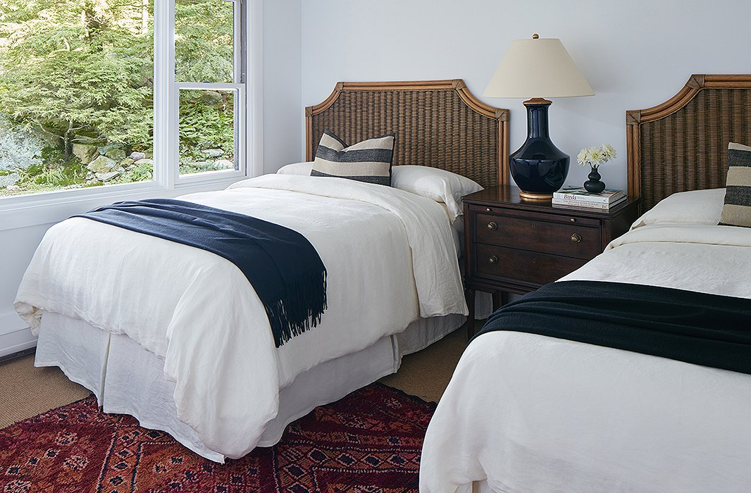 In the other twin guest room, bamboo beds and a vintage rug create a sophisticated but still relaxed retreat. The deep-blue throws and table lamp keep the room cohesive with the rest of the house.
