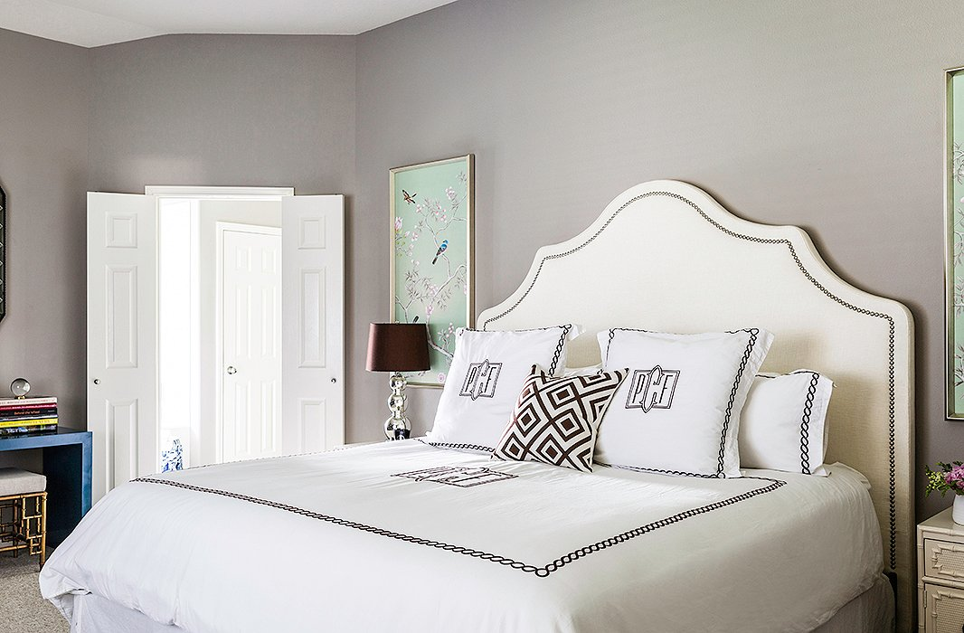 "The master bedroom is one of Paloma's favorite spaces. ""It is kind of a departure from the rest of the home,"" she says. ""It's much more feminine and glamorous."" Adding to the drama are a sumptuous upholstered headboard, monogrammed linens, and silk wall panels on both sides of the bed."