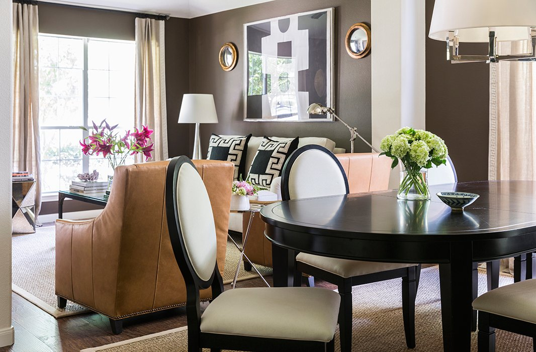 "The dining area, just off the living room, reveals the home's prevailing palette. ""I use black, gray, chocolate brown, and then a few pops of color here and there."" The couple bought the dining table and chairs at a local showroom just before they were married."