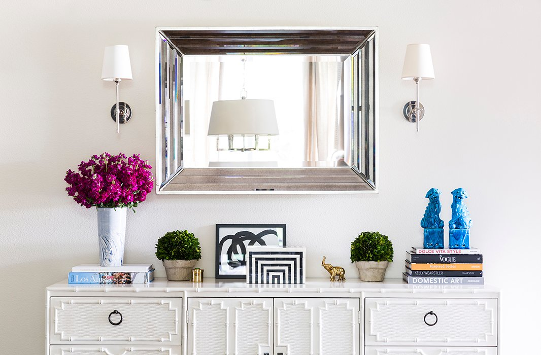 Part of a long hallway, the entry is open to a larger living space; Paloma defined the area without overpowering it. The credenza is from the 1960s and one of the first pieces the couple bought together. The mirror hails from a local store, and the sconces are Thomas O'Brien for Visual Comfort.