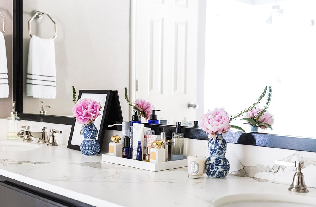 "The master bath boasts a picturesque vanity. ""Everything should have its place and be hidden if possible,"" says Paloma. ""If you don't have room, use trays so it feels neat and collected."" She always opts for timeless materials in baths. ""Think marble, a neutral palette, polished-nickel fixtures, and pretty lighting."""