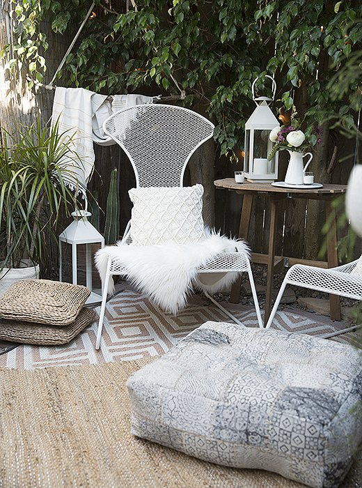 The back garden takes on a Moroccan vibe with low-slung wire chairs, layered rugs, and lots of cozy sheepskin throws, pillows, and cushions.