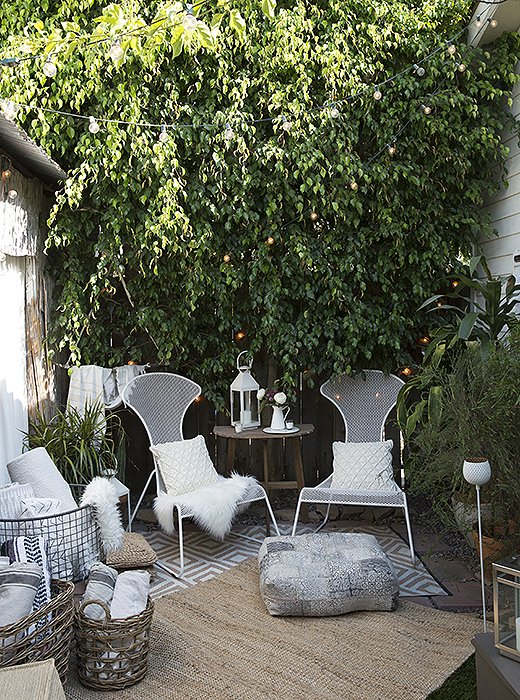 String lights are tucked among the garden's foliage to create an otherworldly canopy. White votive candles and a lantern on the table add more glow factor after the sun sets.