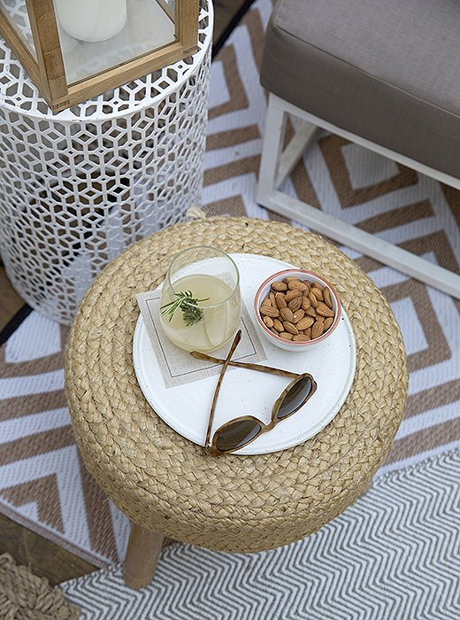 """Whitney often shops for party decor inside her own cottage, bringing out stools, rugs, andpillows. """"It helps polish up the outdoor spaces while providing an extra little touch of comfort for our guests."""""""