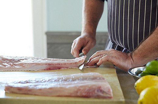 """When putting the fish onto your cutting board, Greg says, """"give it support; always use both hands."""" Even firm-fleshed fish are delicate. Take a chef's knife—not your sharpest one—and start at the tail end, slicing off just the skin on the bottom with a gentle back-and-forth motion."""