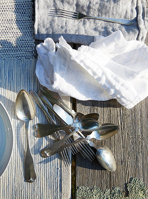 Our picnic table is covered in the pale-green lichen that takes up residence on shingles and porches all over the island. Again, why fight it? A gray-white runner and blue-gray place mats from the Nantucket Looms look just right on the weathered wood.
