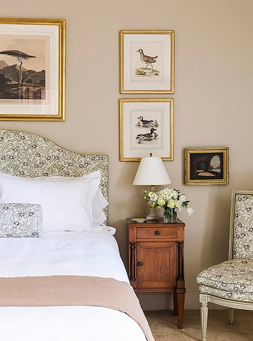 Julia's bedroom is beautifully appointed with a headboard, Louis XVI side chair, and bolster all upholstered in an elegant floral fabric.