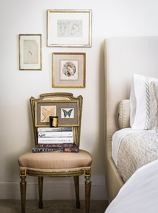 A side chair stacked with books serves as a makeshift nightstand in the author's second bedroom.