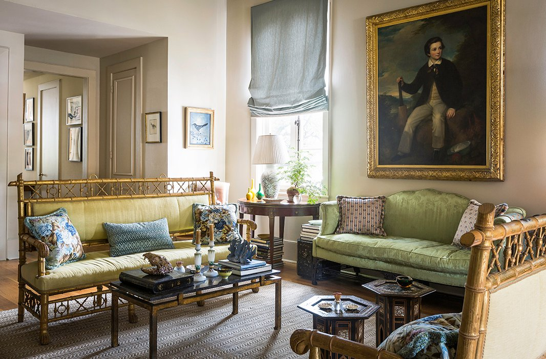 "In her more formal living room, Julia mixes a Chinese Chippendale sofa (which belonged to both her grandmother and her great-grandmother) with a pair of gilded Regency settees and Indian cocktail tables. ""I've become an accidental eclectic,"" she jokes. The author reupholstered the sofa in a green silk damask almost identical to its original silk. Julia found the gilded bamboo benches at Ann Koerner Antiques in New Orleans. ""I saw them and I knew I had to have them,"" Julia says. ""They sat in storage until I had a place to put them. I love any kind of paw feet, and I love bamboo, so they were perfect. And for pieces that look so nutty and over the top, they are really deep and comfortable."""